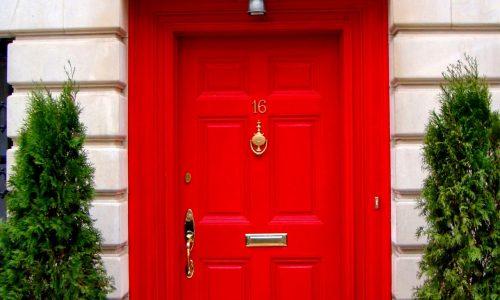 Red front door fitted with door furniture